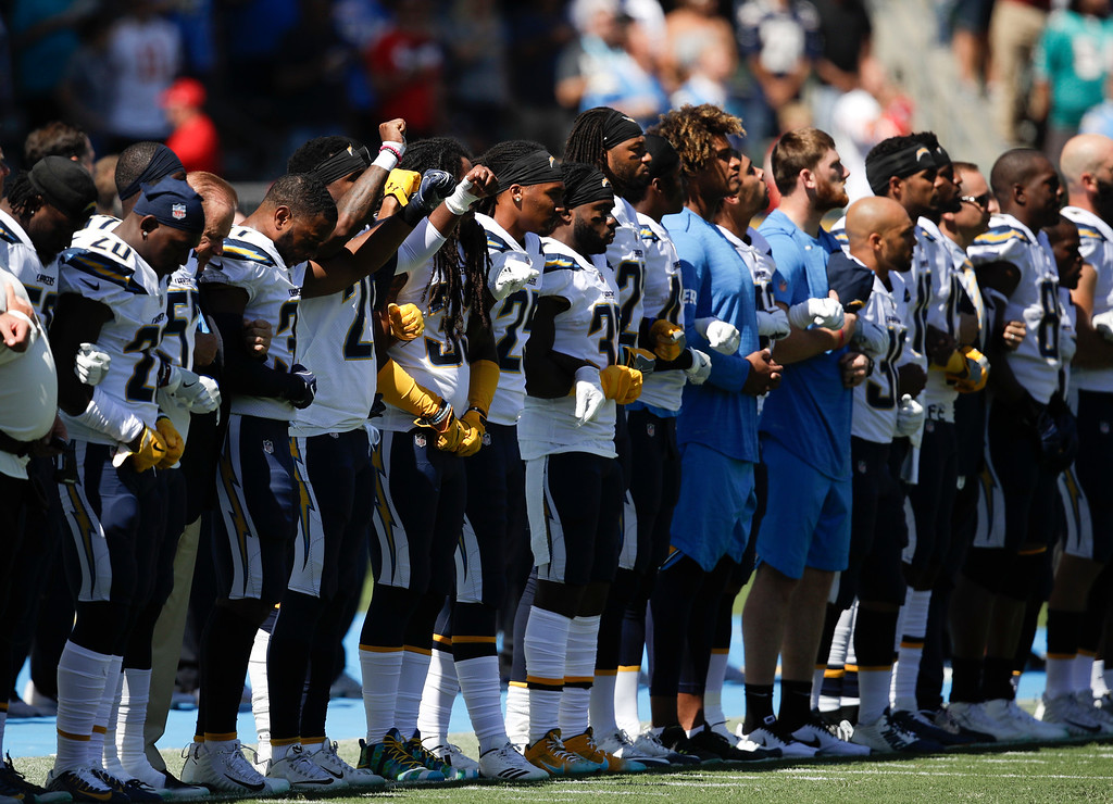. Members of the Los Angeles Chargers link arms during the national anthem before an NFL football game against the Kansas City Chiefs, Sunday, Sept. 24, 2017, in Carson, Calif. (AP Photo/Jae C. Hong)