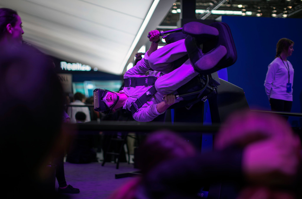 . A visitor laughs using a VR gear installed on a new Samsung Galaxy S9 mobile phone, during the  Mobile World Congress wireless show, in Barcelona, Spain, Monday, Feb 26, 2018. The annual Mobile World Congress (MWC) runs from 26 February - 1 March and draws over 2,300 exhibitors to Barcelona, including industry heavyweights Samsung, Huawei and Nokia. (AP Photo/Emilio Morenatti)