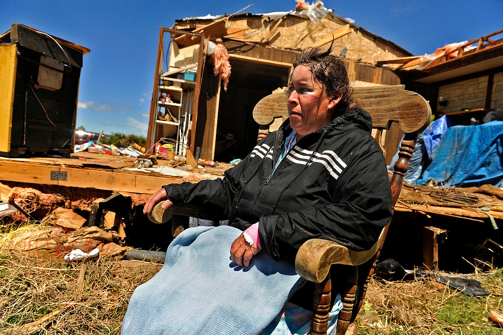 . Lisa Alba\'s family makes her sit down and rest outside her home in Chivington, Colo., after she returned from the hospital, Friday, April, 27, 2012. Alba was thrown from her home when a tornado went through the night before. She had bruises on her face and injured her arm.