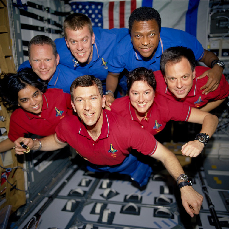 """. STS107-735-032 (16 January - 1 February 2003) --- The STS-107 crew members strike a \""""flying\"""" pose for their traditional in-flight crew portrait in the SPACEHAB Research Double Module (RDM) aboard the Space Shuttle Columbia. From the left (bottom row), wearing red shirts to signify their shift\'s color, are astronauts Kalpana Chawla, mission specialist; Rick D. Husband, mission commander; Laurel B. Clark, mission specialist; and Ilan Ramon, payload specialist. From the left (top row), wearing blue shirts, are astronauts David M. Brown, mission specialist; William C. McCool, pilot; and Michael P. Anderson, payload commander. Ramon represents the Israeli Space Agency. EDITOR\'S NOTE: On February 1, 2003, the seven crew members were lost with the Space Shuttle Columbia over North Texas. This picture was on a roll of unprocessed film later recovered by searchers from the debris."""