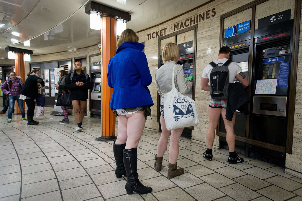 """. Participants in the13th annual International \""""No Pants Subway Ride\"""" queue for tickets at a London underground station in London, on January 12, 2014. Starting in 2002 with only seven participants, the day is now marked in over 60 cities around the world.  The idea behind \""""No Pants\"""" is that random passengers board a subway car at separate stops in the middle of winter, without wearing trousers. The participants wear all of the usual winter clothing on their top half such as hats, scarves and gloves and do not acknowledge each other\'s similar state of undress.  LEON NEAL/AFP/Getty Images"""