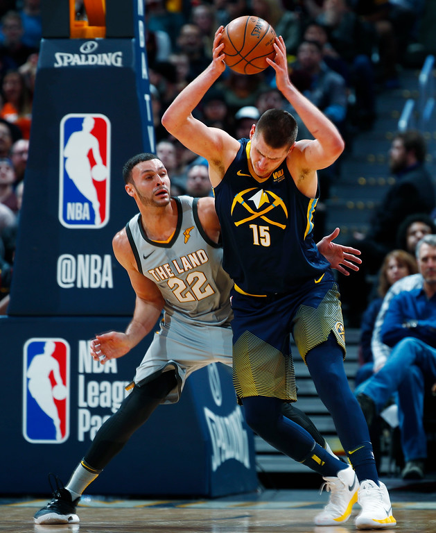 . Denver Nuggets center Nikola Jokic, right, struggles to move the ball as Cleveland Cavaliers forward Larry Nance Jr. defends during the first half of an NBA basketball game Wednesday, March 7, 2018, in Denver. (AP Photo/David Zalubowski)