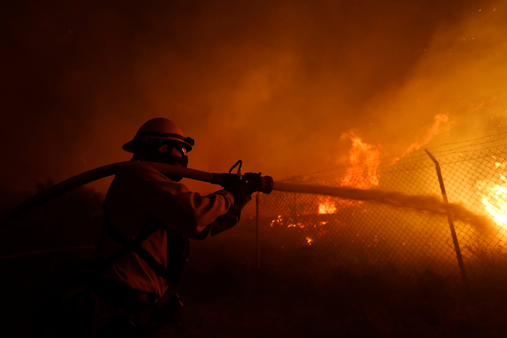 . A firefighter battles to protect a CalTrans Maintenance Station and Fuel Depot from the Springs Fire near Pacific Coast Highway and the Los Angeles County Line at Malibu, California, May 2, 2013. A wind-driven wildfire raging along the California coast north of Los Angeles prompted the evacuation of hundreds of homes and a university campus on Thursday as flames engulfed several farm buildings and recreational vehicles near threatened neighborhoods. REUTERS/Patrick T. Fallon