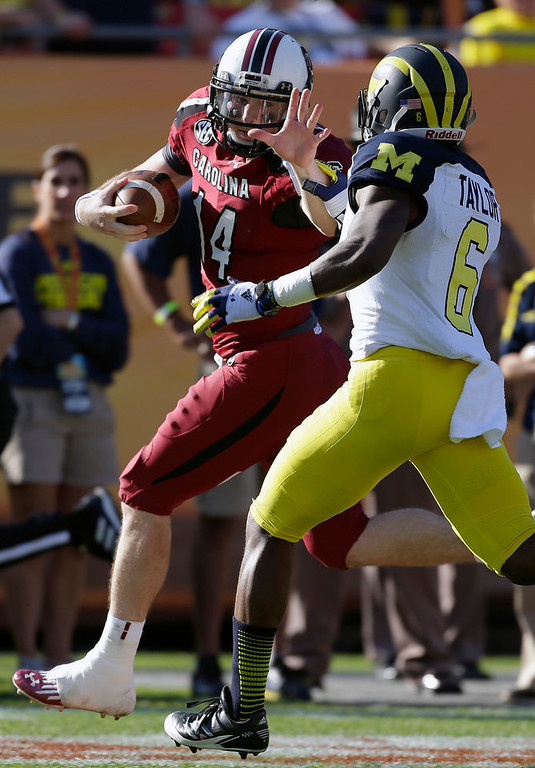 . South Carolina quarterback Connor Shaw (14) prepares to stiff arm Michigan defensive back Raymon Taylor (6) during the second half of the Outback Bowl NCAA college football game  Tuesday, Jan. 1, 2013, in Tampa, Fla. South Carolina won the game 33-28. (AP Photo/Chris O\'Meara)