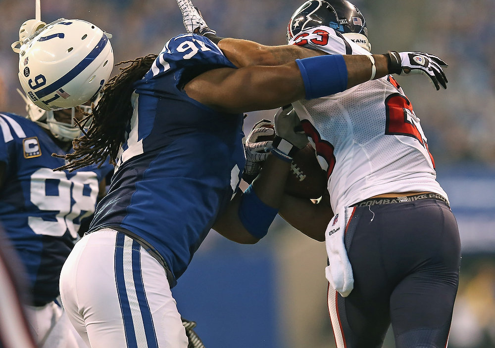 . Ricardo Matthews #91 of the Indianapolis Colts looses his helmet trying to tackle Arian Foster #23 of the Houston Texans at Lucas Oil Stadium on December 30, 2012 in Indianapolis, Indiana. The Colts defeated the Texans 28-16.(Photo by Jonathan Daniel/Getty Images)