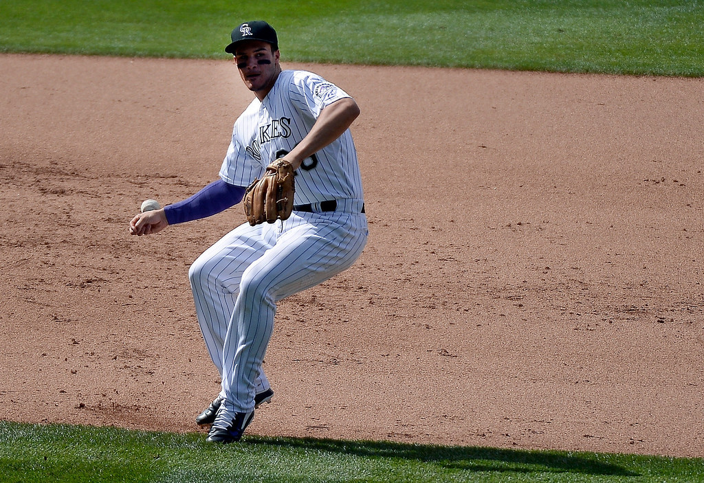 . Colorado Rockies third baseman Nolan Arenado (28) deflects the ball on a single by New York Mets center fielder Juan Lagares (12) during the 6th inning May 4, 2014 at Coors Field. (Photo by John Leyba/The Denver Post)