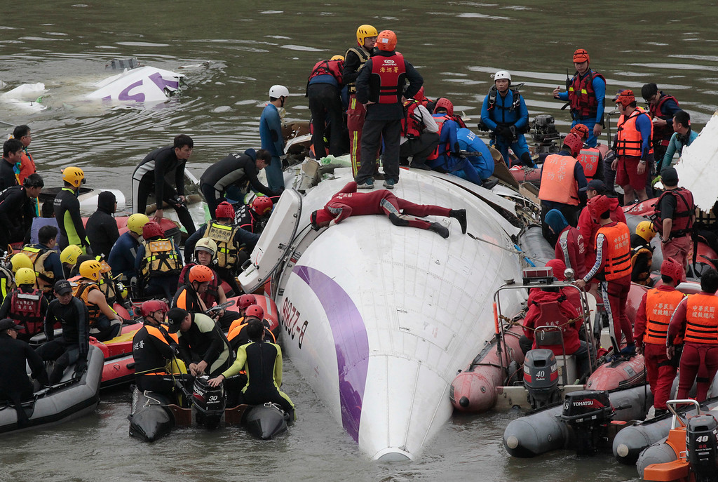 . Emergency personnel try to extract passengers from a commercial plane after it crashed in Taipei, Taiwan, Wednesday, Feb. 4, 2015. The Taiwanese commercial flight with 58 people aboard clipped a bridge shortly after takeoff and crashed into a river in the island\'s capital on Wednesday morning.  (AP Photo/Wally Santana)