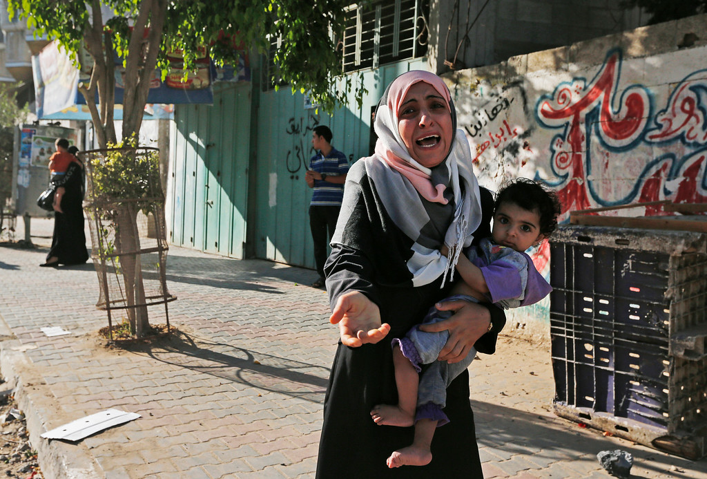 . A woman cries as Palestinians flee their homes in the Shajaiyeh neighborhood of Gaza City, after Israel had airdropped leaflets warning people to leave the area, Wednesday, July 16, 2014. A Hamas website says Israel has fired missiles at the homes of four of its senior leaders as it resumed bombardment of Gaza, following a failed Egyptian cease-fire effort. Health officials say the Palestinian death toll in nine days of fighting has reached 204. (AP Photo/Lefteris Pitarakis)