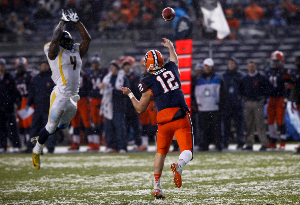 Description of . Ryan Nassib #12 of the Syracuse Orang passes over Josh Francis #4 of the West Virginia Mountaineers in the New Era Pinstripe Bowl at Yankee Stadium on December 29, 2012 in the Bronx borough of New York City.  (Photo by Jeff Zelevansky/Getty Images)