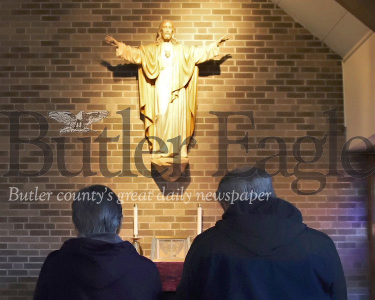Terry  and Jo Faber pray Thursday morning at St. Fidelis Roman Catholic Church in Meridian. Seb Foltz/Butler Eagle