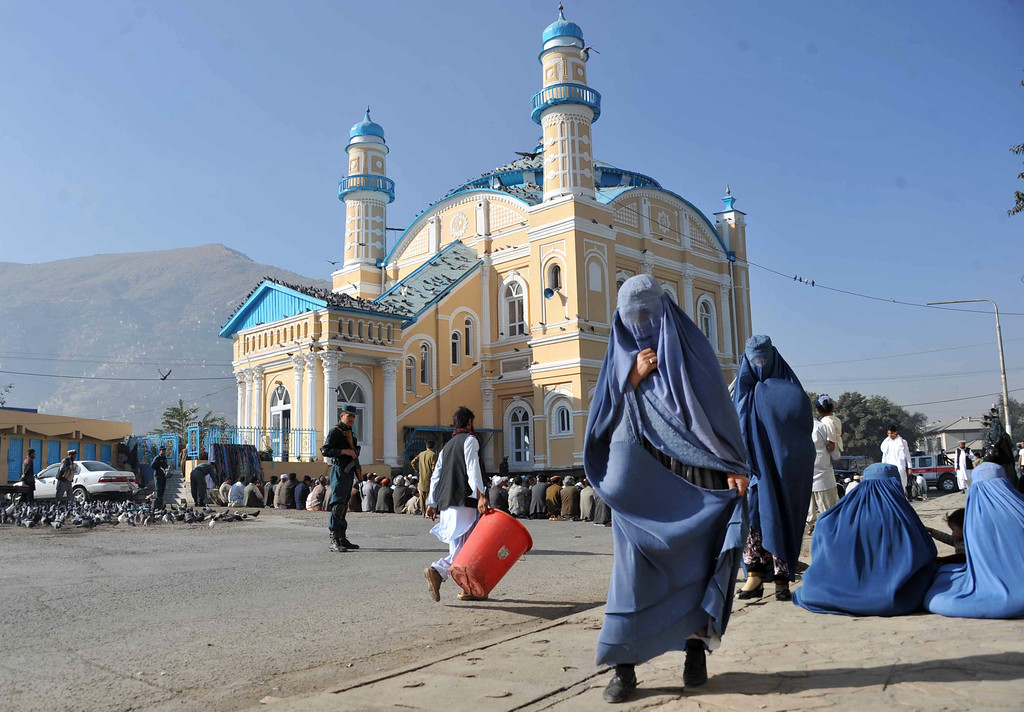 . Afghan women walk past Muslim devotees praying to celebrate Eid al-Adha at the Shah-e Do Shamshira mosque in Kabul on October 15, 2013.  AFP PHOTO/ Noorullah  Shirzada/AFP/Getty Images