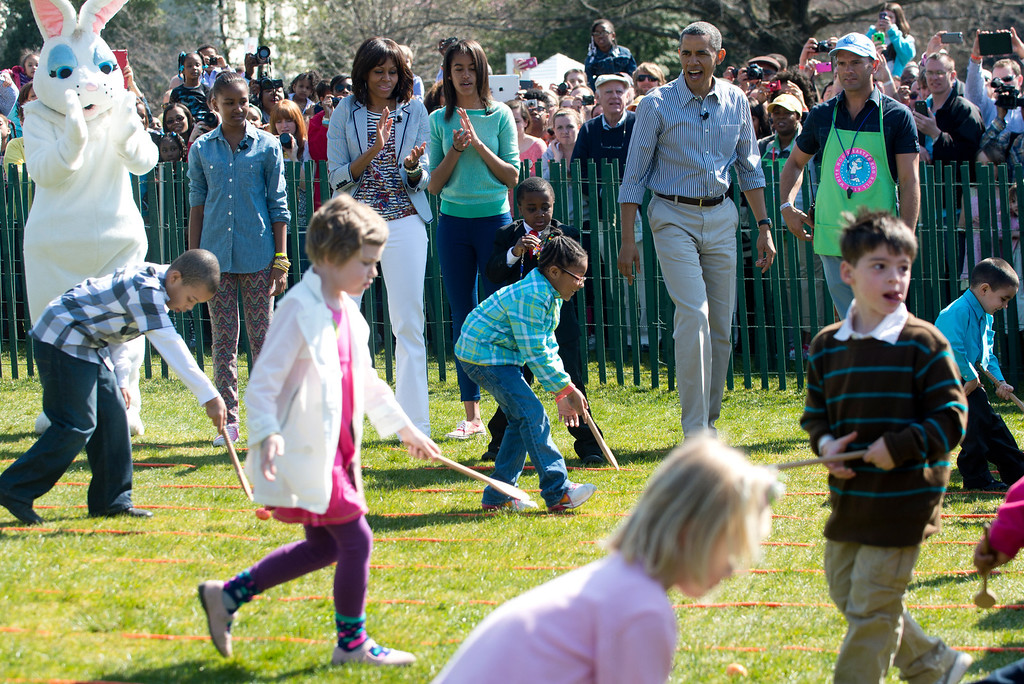 . US President Barack Obama and First Lady Michelle Obama, daughters Sasha(2nd-L-Rear) and Malia(C-rear) and The Easter Bunny, cheer on as children race to roll eggs as they participate in the White House Easter Egg Roll on the South Lawn of the White House in Washington, DC, April 1, 2013. Obama hosts the annual event, featuring live music, sports courts, cooking stations, storytelling and Easter egg rolling. AFP PHOTO / Saul  LOEB/AFP/Getty Images