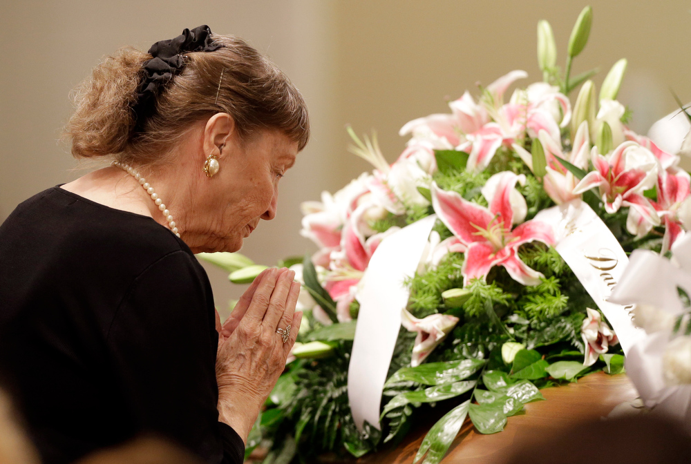 . An unidentified woman prays at the casket of country music star Mindy McCready during a funeral ceremony at the Crossroads Baptist Church in Fort Myers, Fla.,Tuesday, Feb. 26, 2013. McCready committed suicide Feb. 17 at her home in Arkansas, days after leaving a court-ordered substance abuse program. (AP Photo/Alan Diaz)