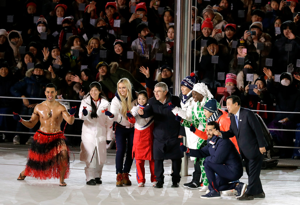 . Athletes from various nations including Pita Taufatofua, of Tonga, at left, United States\' Lindsey Vonn, third from left, and Thomas Bach, president of the International Olympic Committee, fifth from left, pose for photos during the closing ceremony of the 2018 Winter Olympics in Pyeongchang, South Korea, Sunday, Feb. 25, 2018. (AP Photo/Michael Probst)