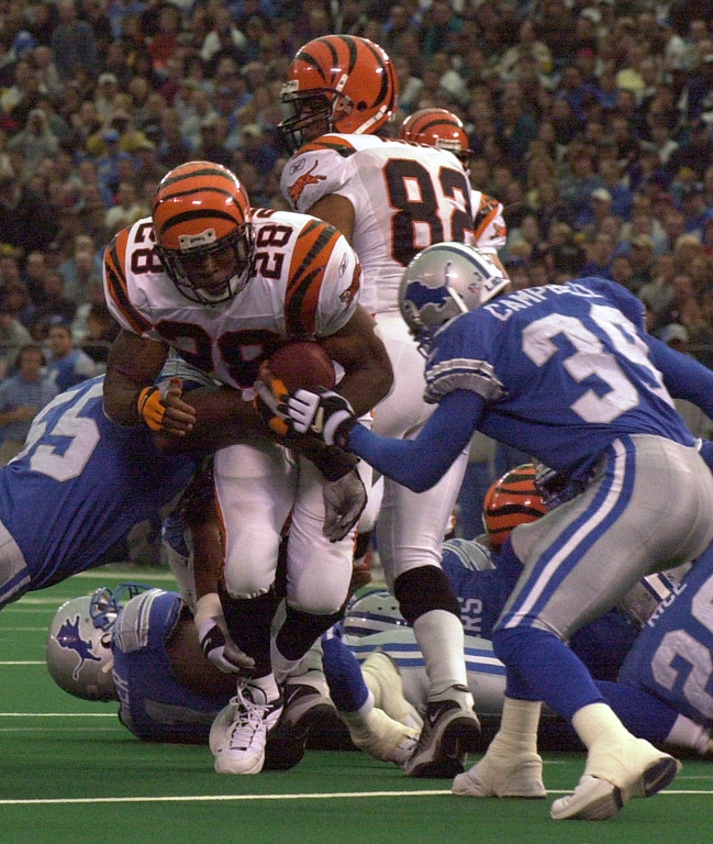 . Corey Dillon (28) of the Cincinnati Bengals drives past Detroit Lions players Allen Aldridge (55) and Lamar Campbell (39) to pick a first down nera the goal line in the first half during Sunday\'s game played at the Pontiac Silverdome. The Lions lost 31-27 to the Bengals.