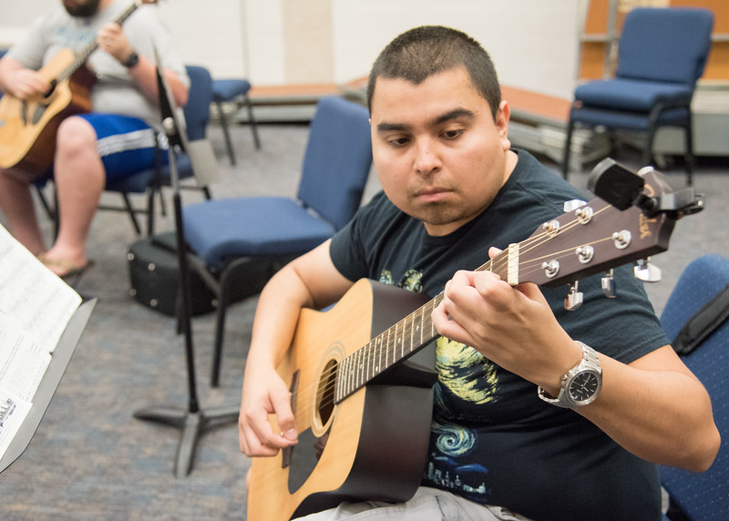 Justin Ferdin works on his guitar during class.