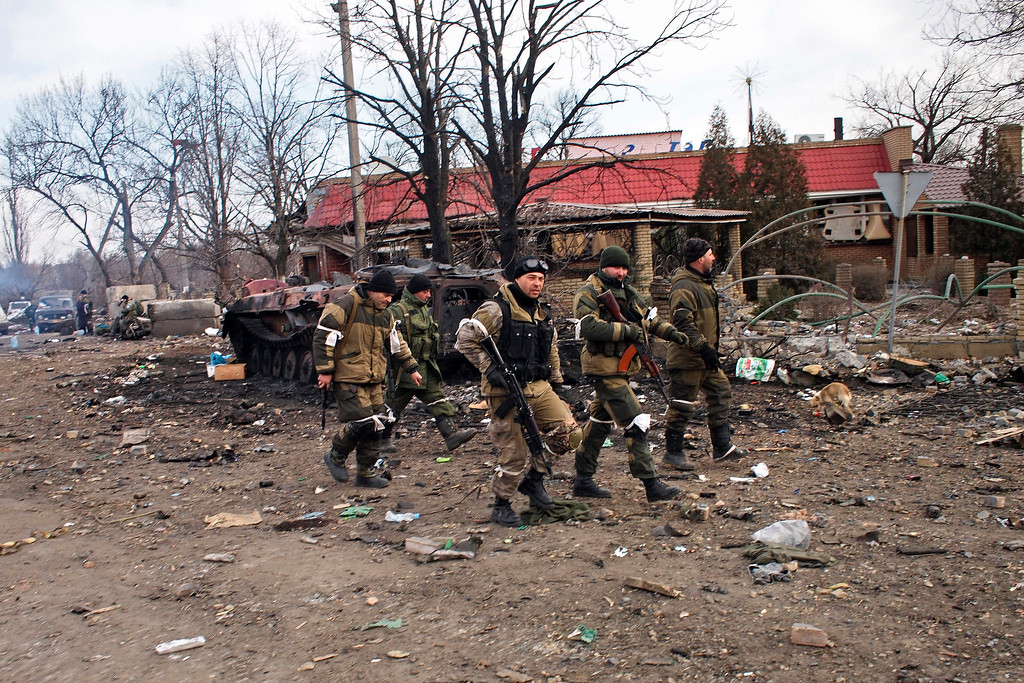 . Pro-Russia rebels walk in Debaltseve, eastern Ukraine on Thursday, Feb. 19, 2015. After weeks of relentless fighting, the embattled Ukrainian rail hub of Debaltseve fell Wednesday to Russia-backed separatists, who hoisted a flag in triumph over the town. The Ukrainian president confirmed that he had ordered troops to pull out and the rebels reported taking hundreds of soldiers captive. (AP Photo/ Peter Leonard)