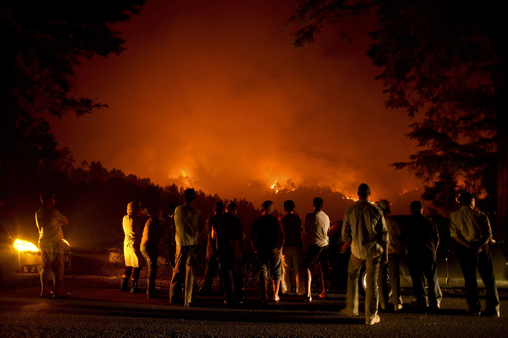 . People stand watching a wildfire in Santiago de Besteiros, near Caramulo, central Portugal, on August 30, 2013. Five Portuguese mountain villages were evacuated overnight as forest fires intensified in the country\'s north and centre, officials said today.   AFP PHOTO / PATRICIA DE MELO  MOREIRA/AFP/Getty Images