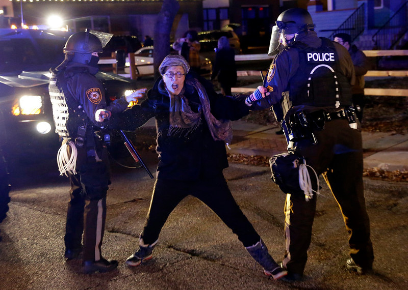 . Police officers grab a protester after the announcement of the grand jury decision, Monday, Nov. 24, 2014, in Ferguson, Mo. A grand jury has decided not to indict Ferguson police officer Darren Wilson in the shooting death of 18-year-old Michael Brown. (AP Photo/David Goldman)