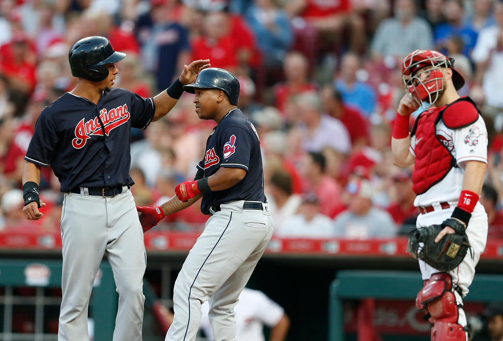 . Cleveland Indians\' Jose Ramirez, center, is congratulated on a two run home run off Cincinnati Reds starting pitcher Homer Bailey by Michael Brantley, left, during the third inning of a baseball game, Monday, Aug. 13, 2018, in Cincinnati. At right is Cincinnati Reds catcher Tucker Barnhart. (AP Photo/Gary Landers)
