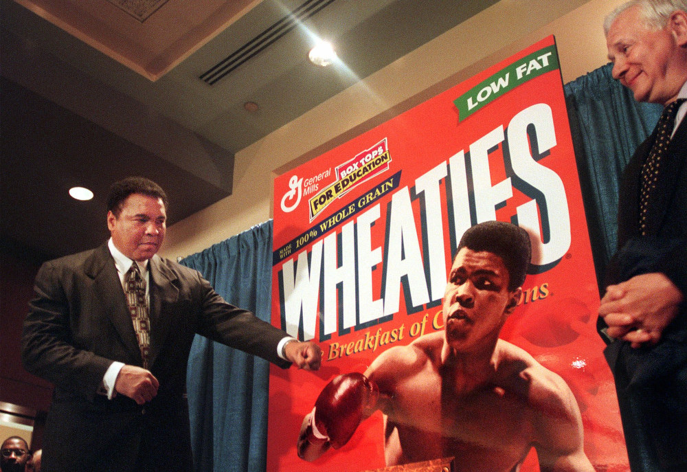 Description of . Muhammad Ali, known as 'The Greatest,' punches at a poster of the Wheaties 'The Breakfast of Champions' cereal during the unveiling of the 75th Anniversary cereal box in his honor in New York, Thursday, February 4, 1999. ESPN sports commentator Dick Shaap, right, who hosted the event, says he owes his career to Ali who changed the business of professional sports. Wheaties recognized Ali as the most 'recognized sports figure' of our time for the 75th anniversary celebration.  (AP Photo/Bebeto Matthews)
