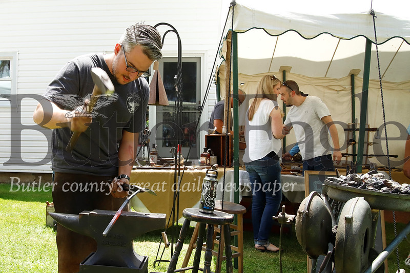 Slippery Rock blacksmithing artist Kyle Gercken of Forged in Kol hammers out what will become a decorative hook, while manning his booth at Whispering Pines. Seb Foltz/ Butler Eagle