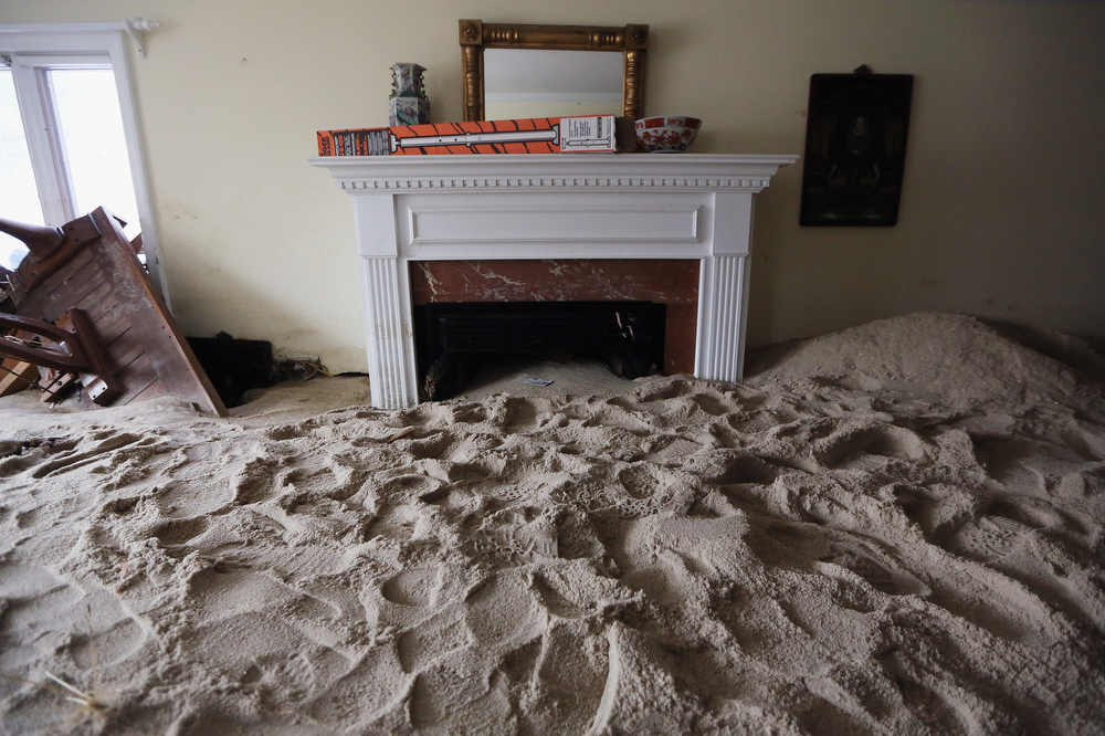 Description of . A living room is filled with sand washed in by Superstorm Sandy on November 14, 2012 in Point Pleasant Beach, New Jersey. Many residents of the hard hit seaside town remain without power following Superstorm Sandy. (Photo by Mario Tama/Getty Images)