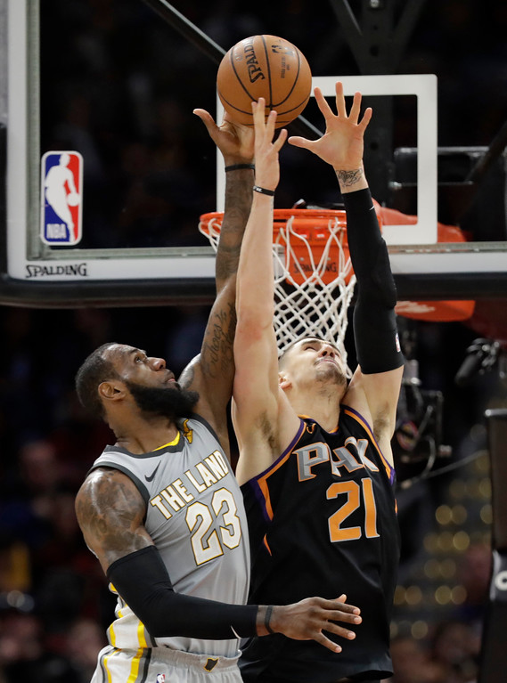 . Cleveland Cavaliers\' LeBron James (23) and Phoenix Suns\' Alex Len (21) reach for the ball during the second half of an NBA basketball game Friday, March 23, 2018, in Cleveland. The Cavaliers won 120-95. (AP Photo/Tony Dejak)