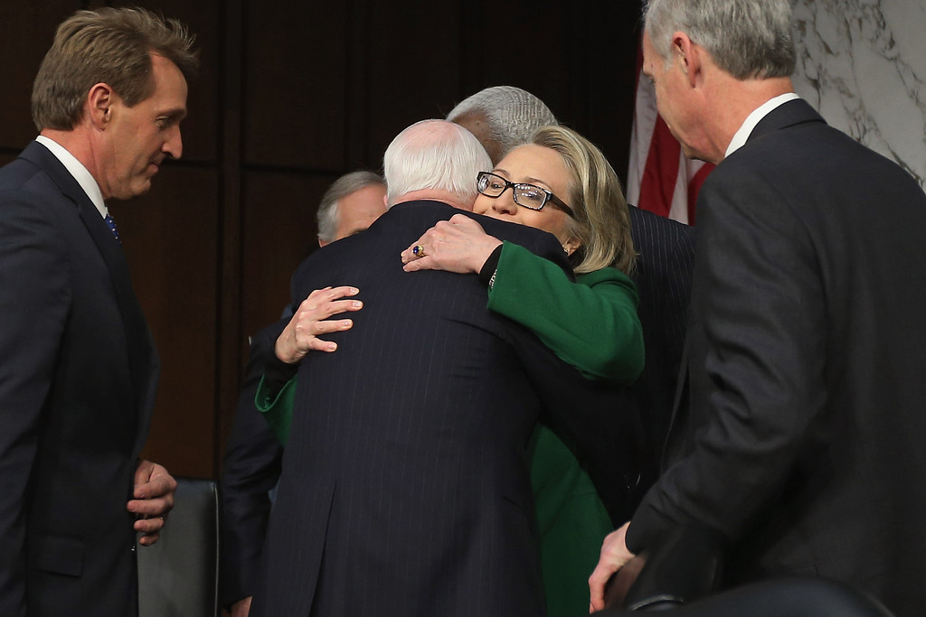 . WASHINGTON, DC - JANUARY 23:  U.S. Secretary of State Hillary Clinton embraces Sen. John McCain (R-AZ) as  Senate Foreign Relations Committee members Sen. Jeff Flake (R-AZ) (L) and Sen. Ron Johnson (R-WI) look on before a hearing with the Senate Foreign Relations Committee on Capitol Hill January 23, 2013 in Washington, DC. Lawmakers questioned Clinton about the security failures during the September 11 attacks against the U.S. mission in Benghazi, Libya, that led to the death of four Americans, including U.S. Ambassador Christopher Stevens. (Photo by Chip Somodevilla/Getty Images)