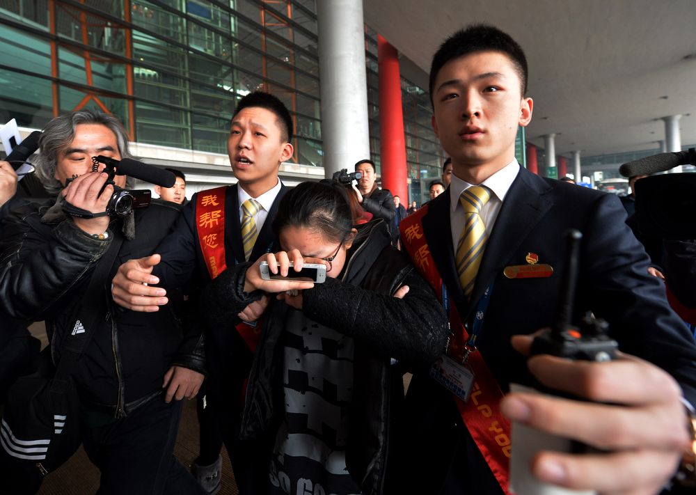 . A crying woman is escorted to a bus for relatives at the Beijing Airport after news of the missing Malaysia Airlines Boeing 777-200 plane on March 8, 2014.  Malaysia Airlines said a flight carrying 239 people from Kuala Lumpur to Beijing went missing early on March 8, and the airline was notifying next of kin in a sign it expected the worst. (MARK RALSTON/AFP/Getty Images)