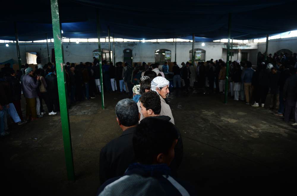 . Afghan residents line up to vote inside a polling station in Kabul on April 5, 2014. Afghan voters went to the polls to choose a successor to President Hamid Karzai, braving Taliban threats in a landmark election held as US-led forces wind down their long intervention in the country. Afghanistan\'s third presidential election brings an end to 13 years of rule by Karzai, who has held power since the Taliban were ousted in a US-led invasion in 2001, and will be the first democratic handover of power in the country\'s turbulent history.   (SHAH MARAI/AFP/Getty Images)