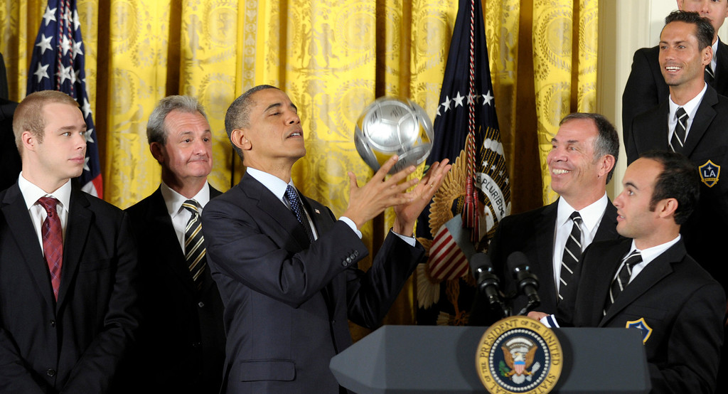. President Barack Obama catches a soccer ball after bouncing it off of his head during an event in the East Room of the White House in Washington, Tuesday, March 26, 2013, to honor the 2012 championship seasons of the Stanley Cup hockey champion Los Angeles Kings and the Major League Soccer champion Los Angeles Galaxy. From second from left are, Kings coach Darryl Sutter, the president, Galaxy coach Bruce Arena and Galaxy forward Landon Donovan.  (AP Photo/Susan Walsh)