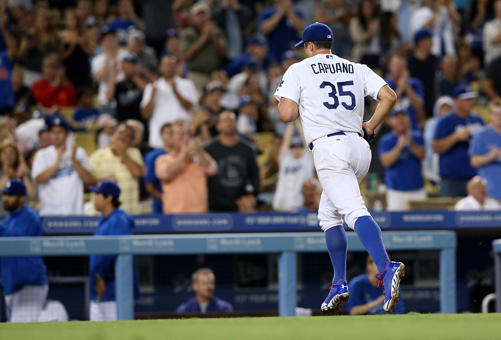 . Starting pitcher Chris Capuano #35 of the Los Angeles Dodgers runs off the field to cheers as he is relieved in th seventh inning after pitching 6 1/3 scoreless innings against the Colorado Rockies at Dodger Stadium on July 11, 2013 in Los Angeles, California.  (Photo by Stephen Dunn/Getty Images)