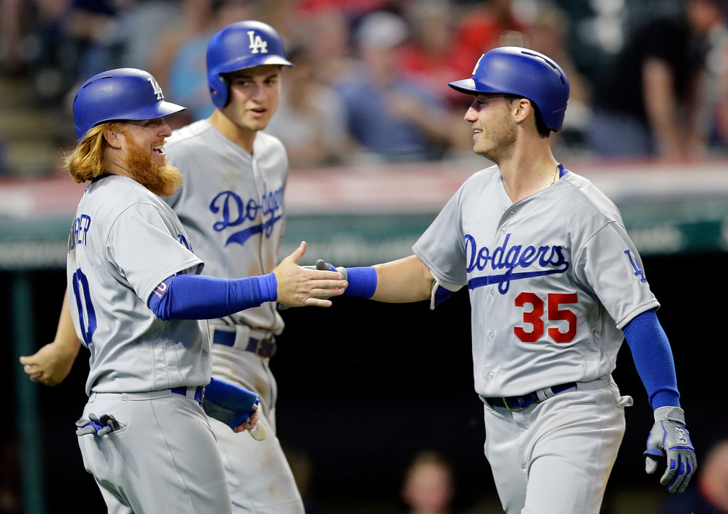 . Los Angeles Dodgers\' Cody Bellinger, right, is congratulated by Justin Turner, left, as Corey Seager, back, watches during the ninth inning of the team\'s baseball game against the Cleveland Indians, Tuesday, June 13, 2017, in Cleveland. Bellinger hit a three-run home run off Indians relief pitcher Boone Logan. Turner and Seager scored on the play. (AP Photo/Tony Dejak)