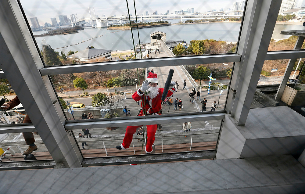 Description of . A window cleaner dressed as Santa Claus works at a shopping mall in Tokyo on Sunday, Dec. 23, 2012. (AP Photo/Shizuo Kambayashi)