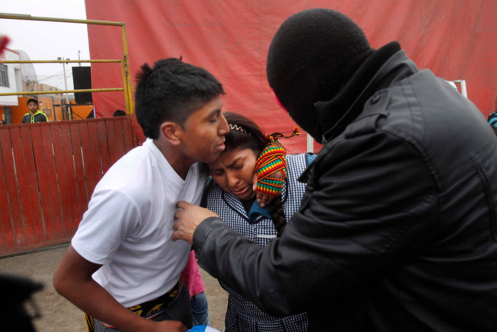 . Clementina Yaguno, center, is comforted by her son Romario Atauquri, left, after he fought in a Takanakuy ritual fight in Lima, Peru. The Andean fight known as Takanakuy is a ritual of unclear providence that predates Spanish colonial rule and happens twice a year, in July and just after Christmas. (AP Photo/Karel Navarro)
