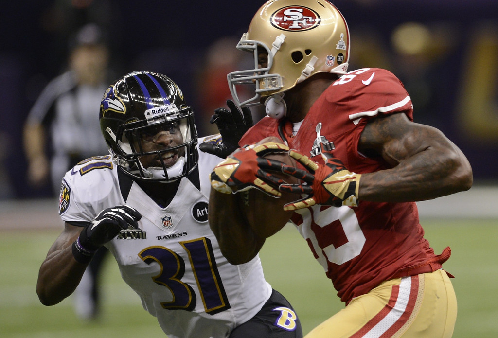 . Bernard Pollard (L) of the Baltimore Ravens eyes Vernon Davis (R) of the San Francisco 49ers during Super Bowl XLVII at the Mercedes-Benz Superdome on February 3, 2013 in New Orleans, Louisiana.     TIMOTHY A. CLARY/AFP/Getty Images
