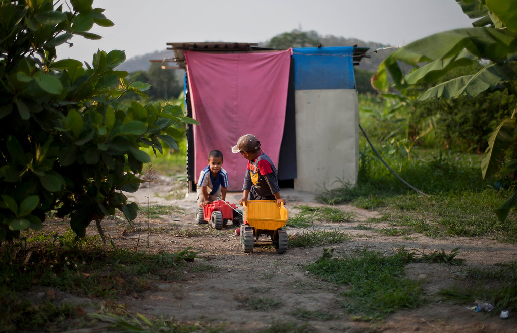 ". In this April 8, 2013 photo, two boys push their toy construction vehicles along a dirt path at a squatter settlement near Tacarigua, Venezuela. Outside Venezuela\'s capital, power outages, food shortages and unfinished projects abound; important factors heading into Sunday\'s election to replace Venezuela\'s late President Hugo Chavez, who died last month after a long battle with cancer. An estimated 2 million of the country\'s nearly 30 million people lack permanent homes, and one of Chavez\'s anti-poverty ""missions\"" builds them. But it\'s been slow going. The government says it has built 370,500 homes and apartments over the past two years, and more than 3 million people applied for them. (AP Photo/Ramon Espinosa)"