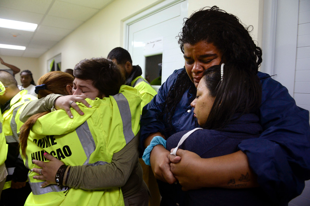 . Rescue team members Candida Lozada, left, and Stephanie Rivera, second from left, Mary Rodriguez, second from right, and Zuly Ruiz, right, embrace as they wait to assist in the aftermath of Hurricane Maria in Humacao, Puerto Rico, Wednesday, Sept. 20, 2017. (AP Photo/Carlos Giusti)