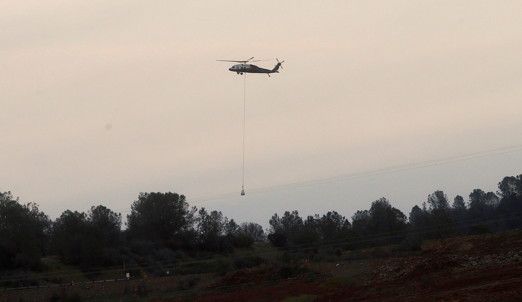 . A helicopter lowers a bag of rocks to be dropped on a hole on the lip of the Oroville Dam\'s emergency spillway Monday, Feb. 13, 2017, in Oroville, Calif. The barrier, at the nation\'s tallest dam, is being repaired a day after authorities ordered mass evacuations for everyone living below the lake out of concerns the spillway could fail. (AP Photo/Rich Pedroncelli)