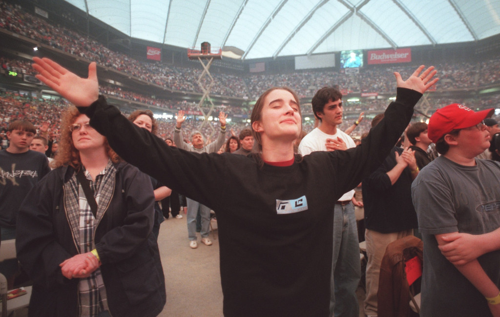 . Emily Tiley , 15 , of Detroit, prays during a song  at the \'Acquire the Fire\'s Day One\' at the Pontiac Silverdome. The event brought thousands of teens to pray , sing and listen to inspirational speeches at the Silverdome Friday evening through the Teen Mania Ministries. The event runs throughout the weekend.  (The Oakland Press /Amy E. Powers)