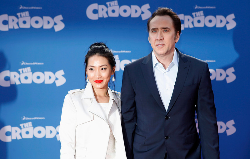 ". Cast member Nicolas Cage and wife Alice Kim (L) arrive for the premiere of the film ""The Croods\"" in New York, March 10, 2013.  REUTERS/Carlo Allegri"