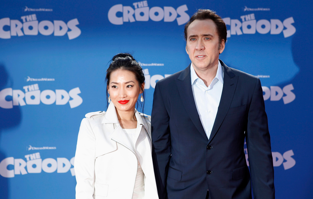 """. Cast member Nicolas Cage and wife Alice Kim (L) arrive for the premiere of the film \""""The Croods\"""" in New York, March 10, 2013.  REUTERS/Carlo Allegri"""