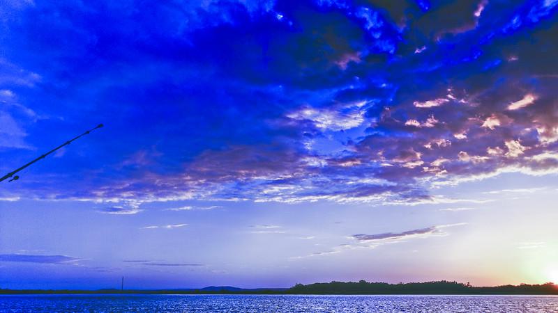Blue coloured cumulus cloud, sunset seascape vista.