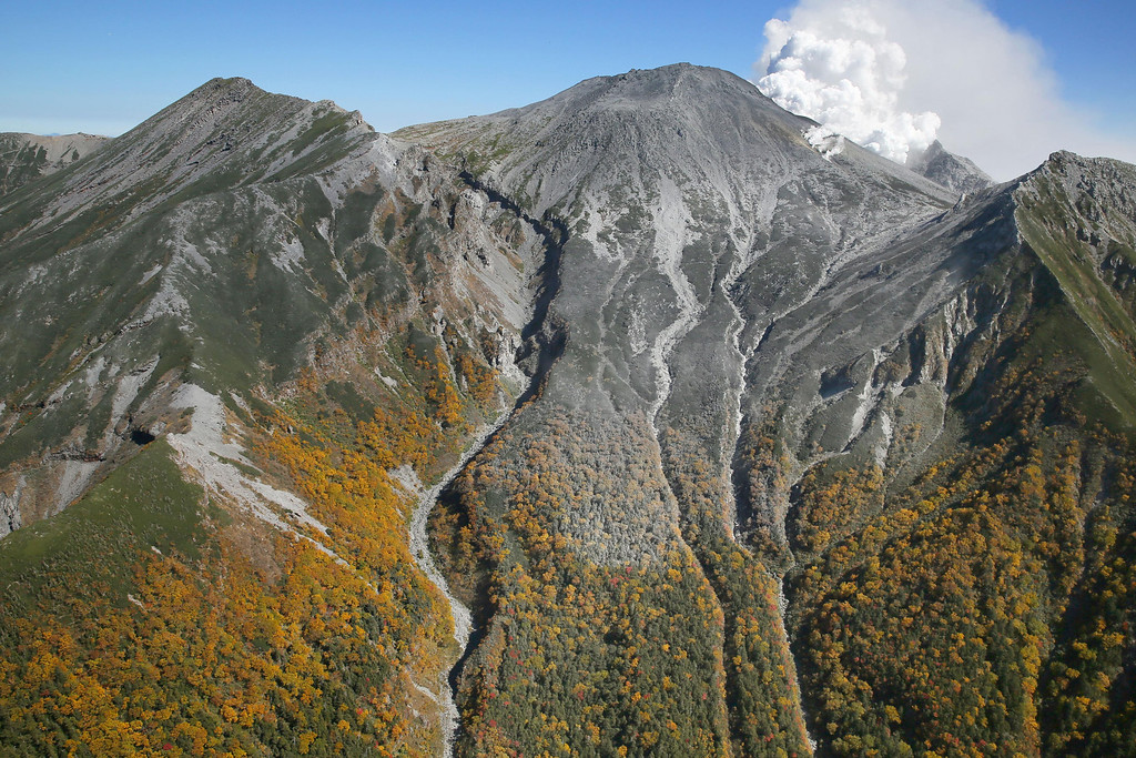. Autumn leaves cover the slopes of Mount Ontake as white plumes of gases and ash are spewed out from the summit crater, central Japan, Monday afternoon, Sept. 29, 2014. Japanese soldiers managed to bring down eight more bodies by helicopter from the ash-blanketed peak of a still-erupting volcano on Monday, before toxic gases and ash forced them to suspend the recovery effort in the early afternoon. (AP Photo/Kyodo News) JAPAN OUT, MANDATORY CREDIT