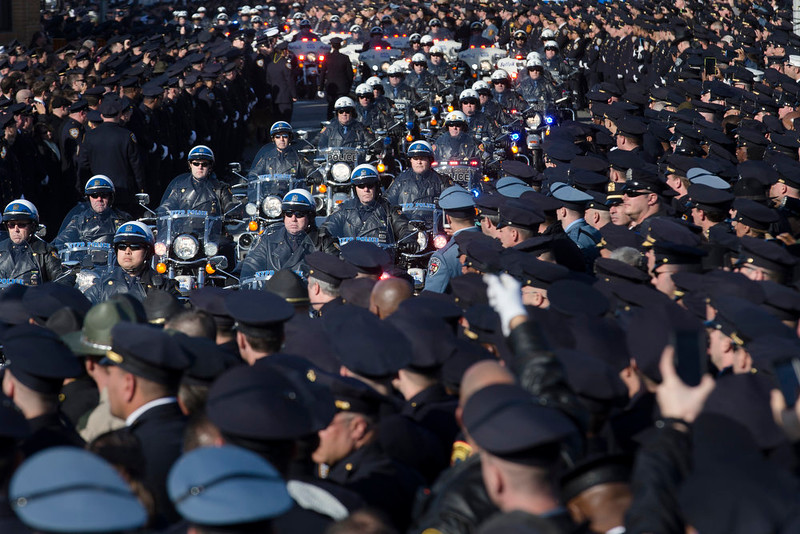 . Motorcycle officers lead the funeral procession of New York city police officer Rafael Ramos in the Glendale section of Queens, Saturday, Dec. 27, 2014, in New York. Ramos and his partner, officer Wenjian Liu, were killed Dec. 20 as they sat in their patrol car on a Brooklyn street. The shooter, Ismaaiyl Brinsley, later killed himself. (AP Photo/John Minchillo)