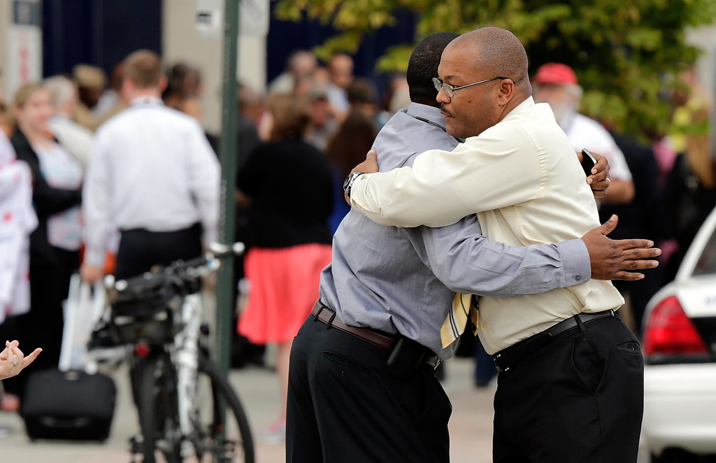 . Two men embrace at a gathering point for family members of Navy Yard employees that was set up inside Nationals Park in the wake of the shooting September 16, 2013 in Washington, DC. Police believe at least one gunman shot and killed at least 12 people and wounded others in an incident that put parts of the city on lockdown. (Photo by Win McNamee/Getty Images)