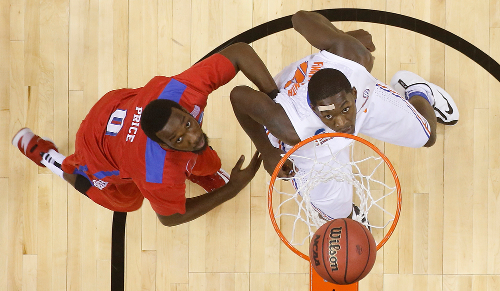 . Florida forward Dorian Finney-Smith (10) watches his shot with Dayton guard Khari Price (0) during the first half in a regional final game at the NCAA college basketball tournament, Saturday, March 29, 2014, in Memphis, Tenn. (AP Photo/John Bazemore)