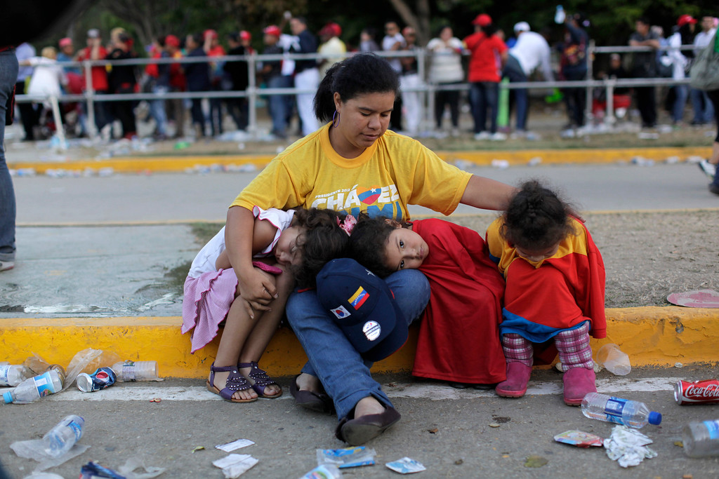 . A woman sits with three girls outside the military academy where a funeral ceremony will take place for Venezuela\'s late President Hugo Chavez in Caracas, Venezuela, Friday, March 8, 2013.  (AP Photo/Rodrigo Abd)