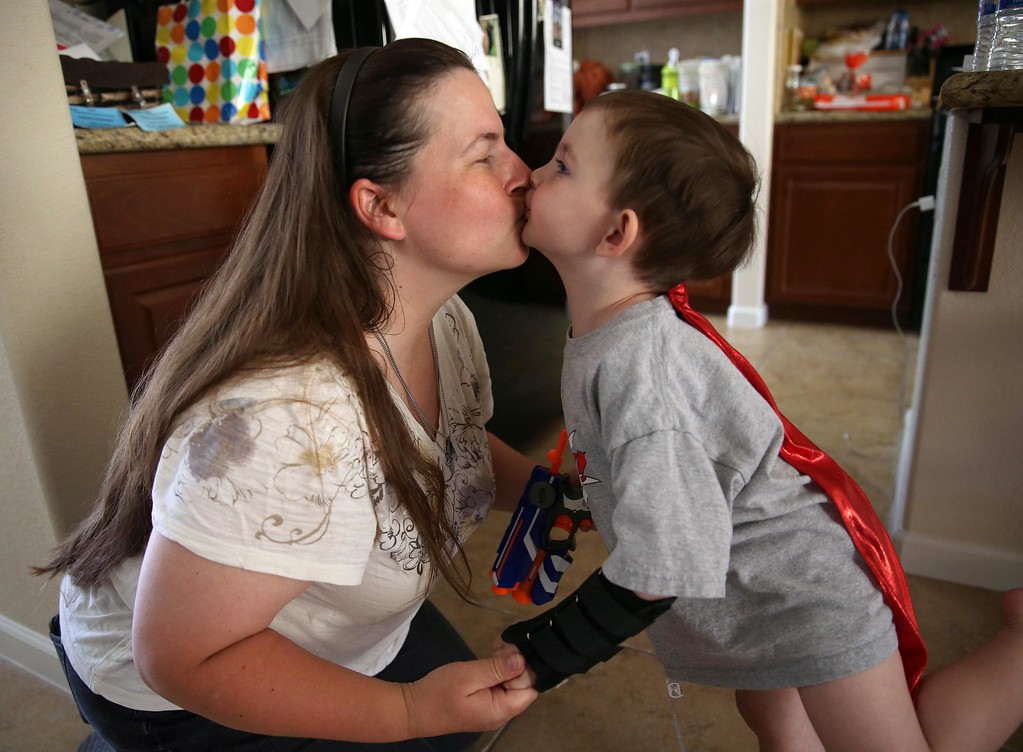 . Matthew Ouimet, 3, gets a kiss from his mom Kristi at their home in Antioch, Calif., on Friday, May 23, 2014. (Jane Tyska/Bay Area News Group)